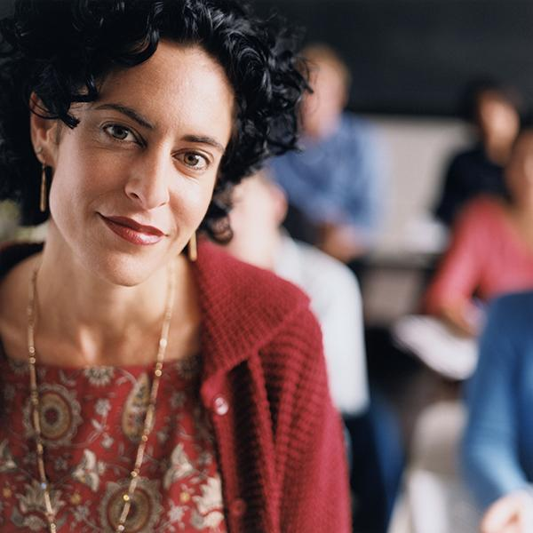 Teacher facing camera, with students visible over her shoulder